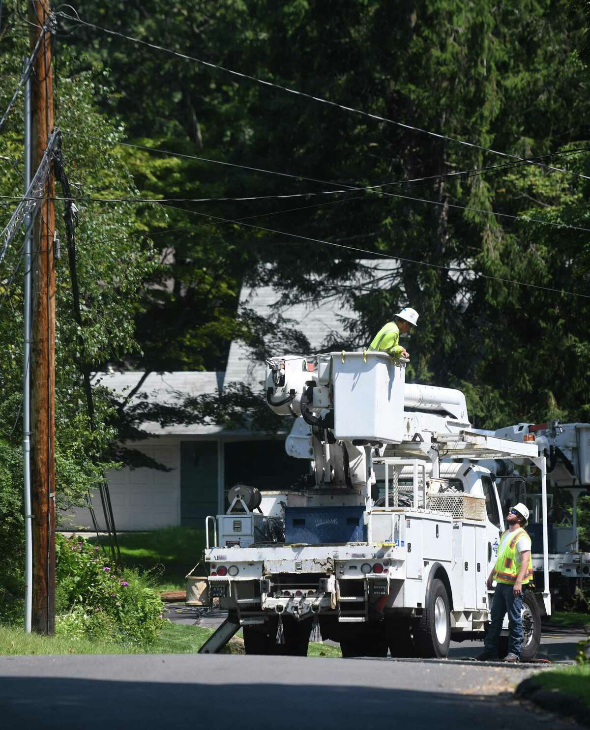 Crews repair powerlines on Angelus Drive in Glenville downed six days after Tropical Storm Isaias hit Greenwich, Conn. Monday, Aug. 10, 2020. Many Eversource customers still remain without power as crews continue scrambling to repair downed powerlines and clean up fallen trees.