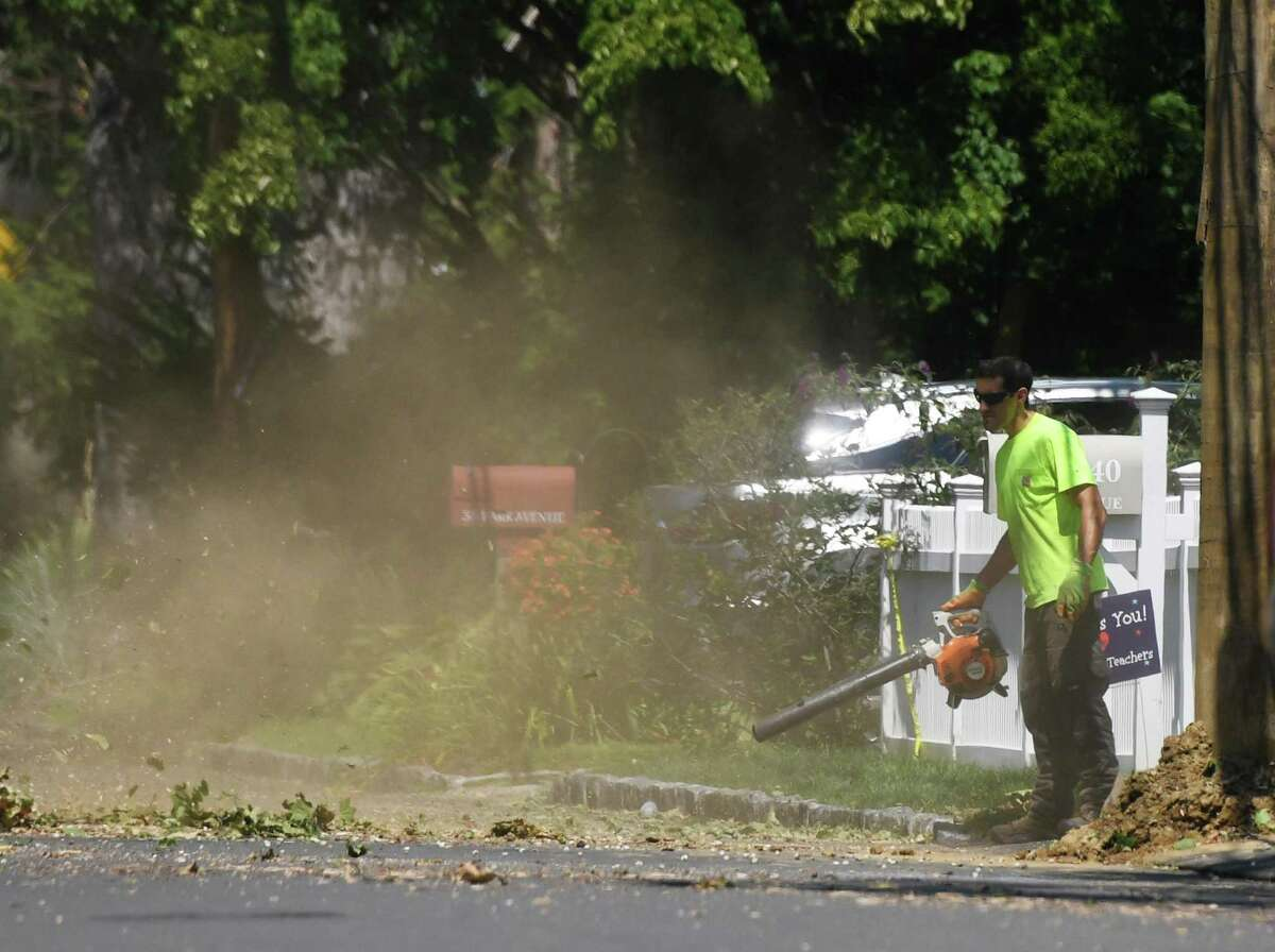 Crews clean up a downed tree on Park Avenue six days after Tropical Storm Isaias hit Old Greenwich, Conn. Monday, Aug. 10, 2020. Many Eversource customers still remain without power as crews continue scrambling to repair downed powerlines and clean up fallen trees.