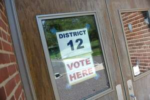 A sign is posted at Greenwich's District 12 polling center at North Mianus School in the Riverside section of Greenwich, Conn. Monday, Aug. 10, 2020. The state's presidential primary election will be held Tuesday after being delayed since April by the coronavirus outbreak.