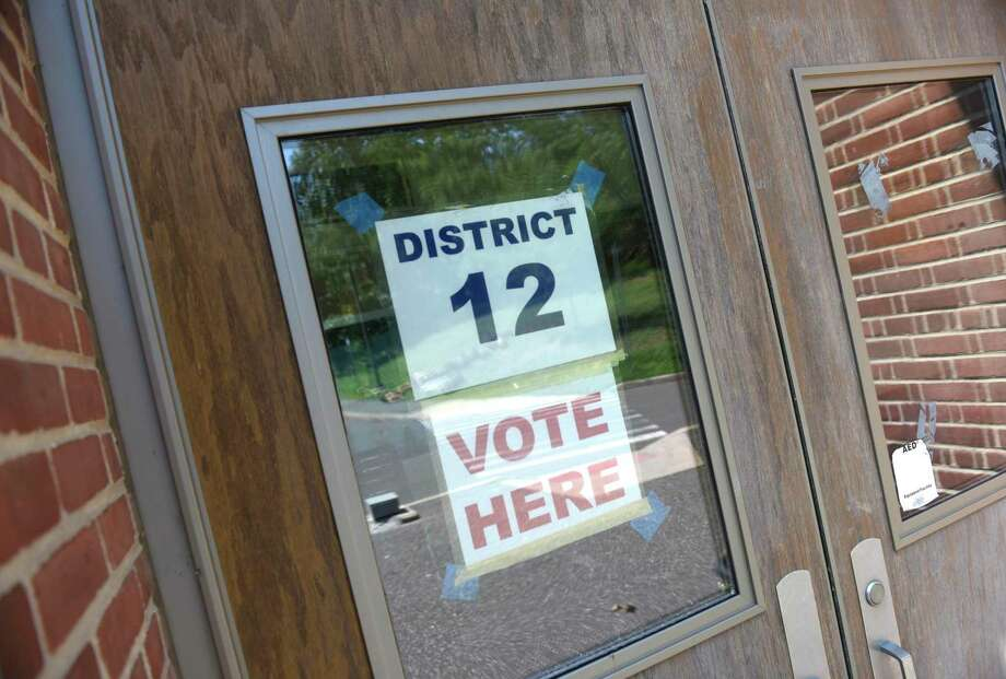 A sign is posted at Greenwich's District 12 polling center at North Mianus School in the Riverside section of Greenwich, Conn. Monday, Aug. 10, 2020. The state's presidential primary election will be held Tuesday after being delayed since April by the coronavirus outbreak. Photo: Tyler Sizemore / Hearst Connecticut Media / Greenwich Time