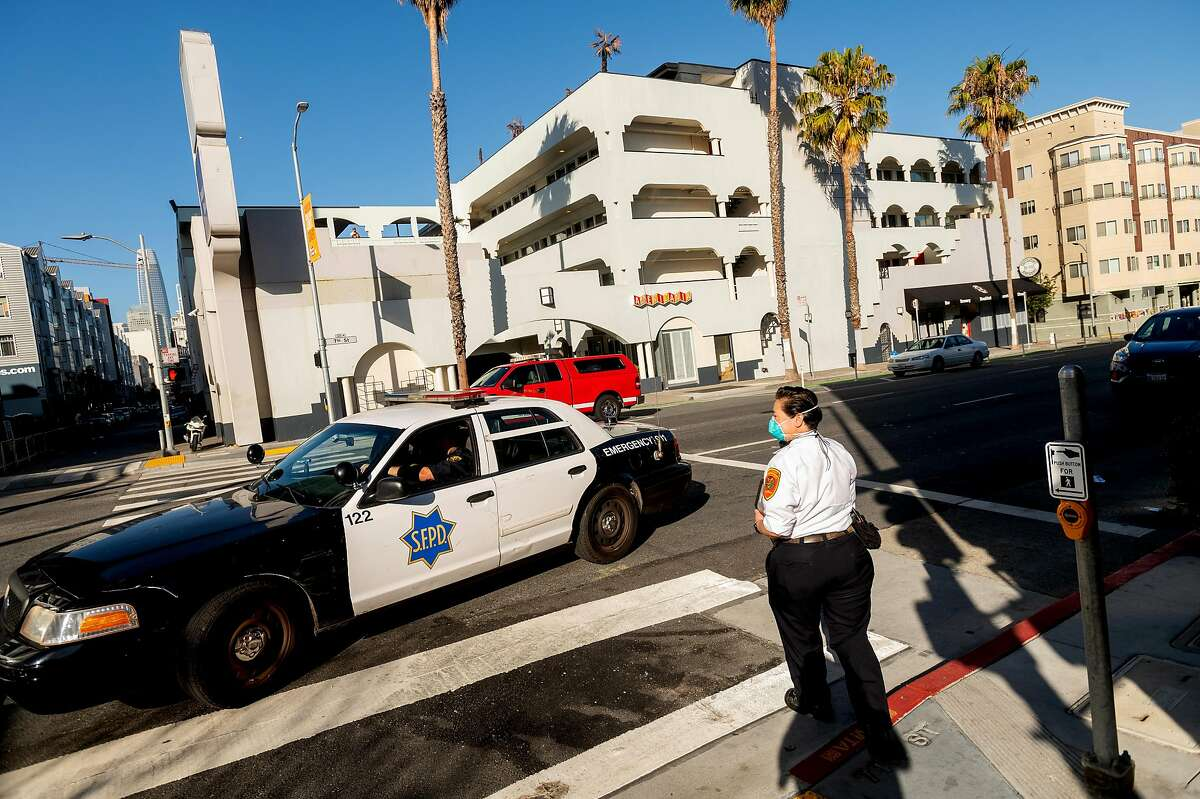 A police car passes EMS6 Captain Jennifer Ishikawa as she leaves a medical call on Friday,. Aug. 7, 2020, in San Francisco.