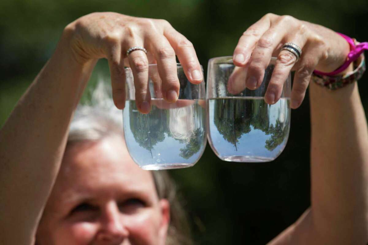 Dr. Teri Albright compares a water sample from her well, left, and compares it to a glass full of bottled water on Monday, May 11, 2020 in Blanco, Texas. After crews working for pipeline giant Kinder Morgan spilled drilling fluid during a boring operation near the Blanco River in late March, several homeowners say their wells were contaminated. Albright's well water has became contaminated.