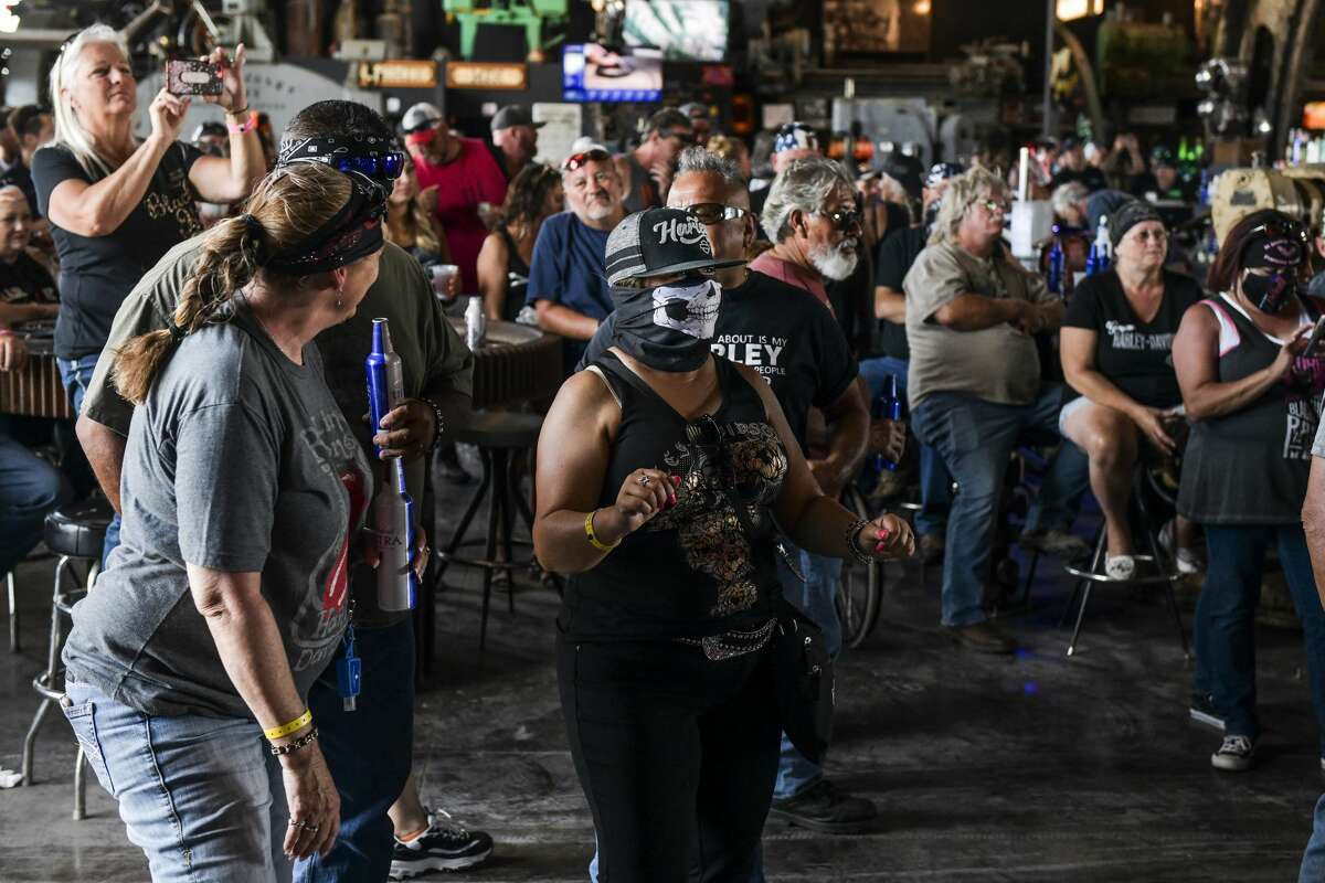 Maggie Zepeda, center, dances as she watches a concert at the Full Throttle Saloon during the 80th Annual Sturgis Motorcycle Rally in Sturgis, South Dakota on August 9, 2020. While the rally usually attracts around 500,000 people, officials estimate that more than 250,000 people may still show up to this year's festival despite the coronavirus pandemic. (Photo by Michael Ciaglo/Getty Images)