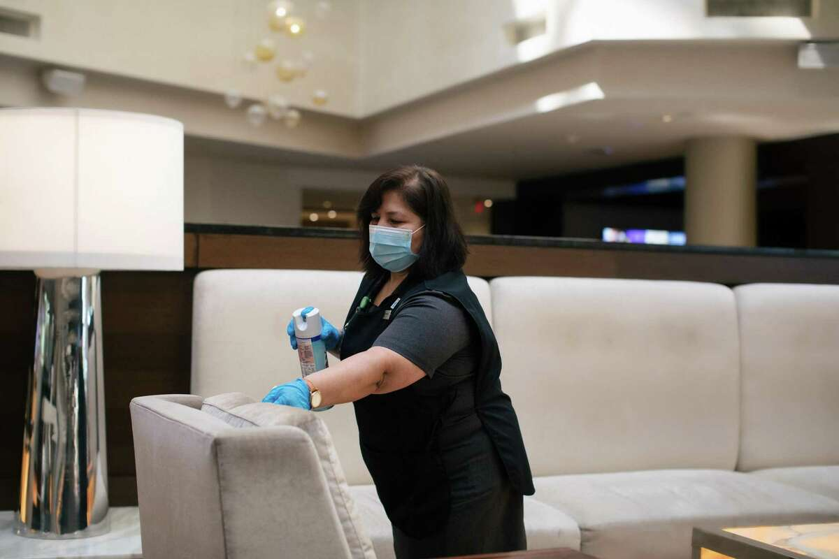 Blanca Renderos cleans a common area at the Hilton McLean Tysons Corner in McLean, Va., July 17, 2020. Faced with a historic downturn due to the coronavirus, hotels nationwide are changing the most basic ways they run their business to show would-be travelers they understand where they're at: terrified. (Alyssa Schukar/The New York Times)
