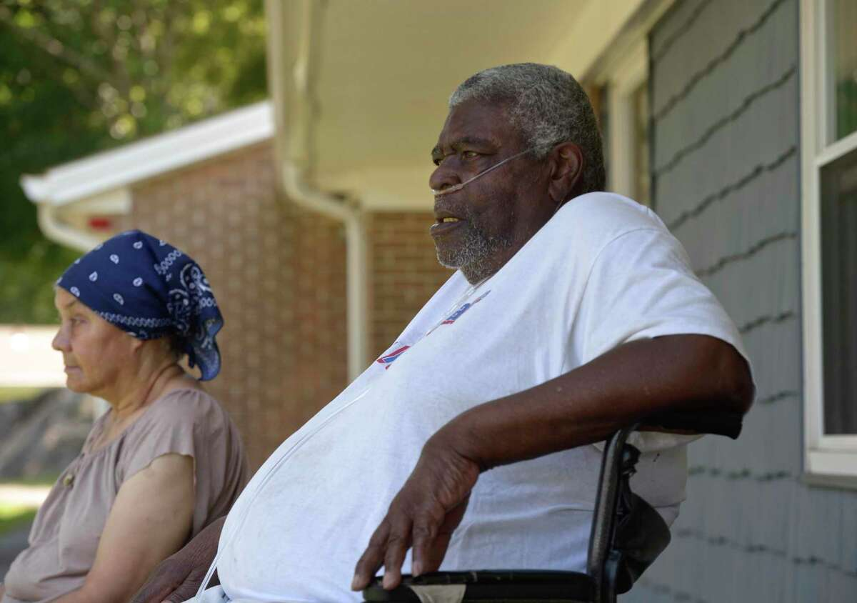Vernal Carr, right, and Senora Peton sit outside in the shade at the Housing Authority of Danbury Glen Apartments on Monday, August 10, 2020. Both had no power in their apartments and Carr was using canisters of oxygen instead of his oxygen machine.