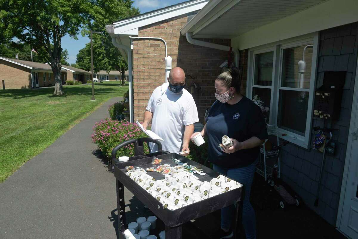 Andre Chmelko, left, and Jessie Castro, both from the Housing Authority of Danbury, distribute lunches to residents of the Glen Apartments on Monday, August 10, 2020.