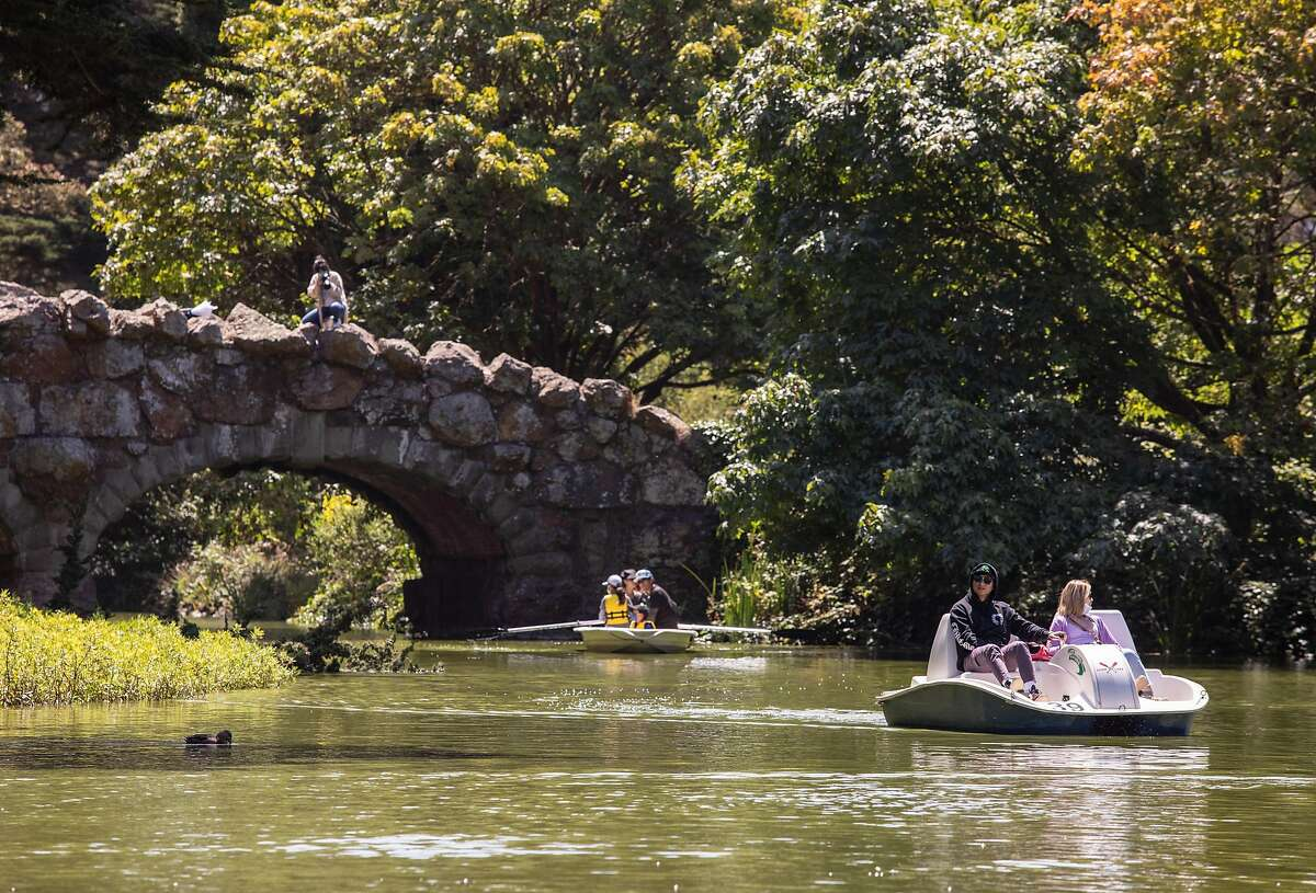 People ride pedal boats at Stow Lake in San Francisco's Golden Gate Park on Saturday, July 25, 2020.