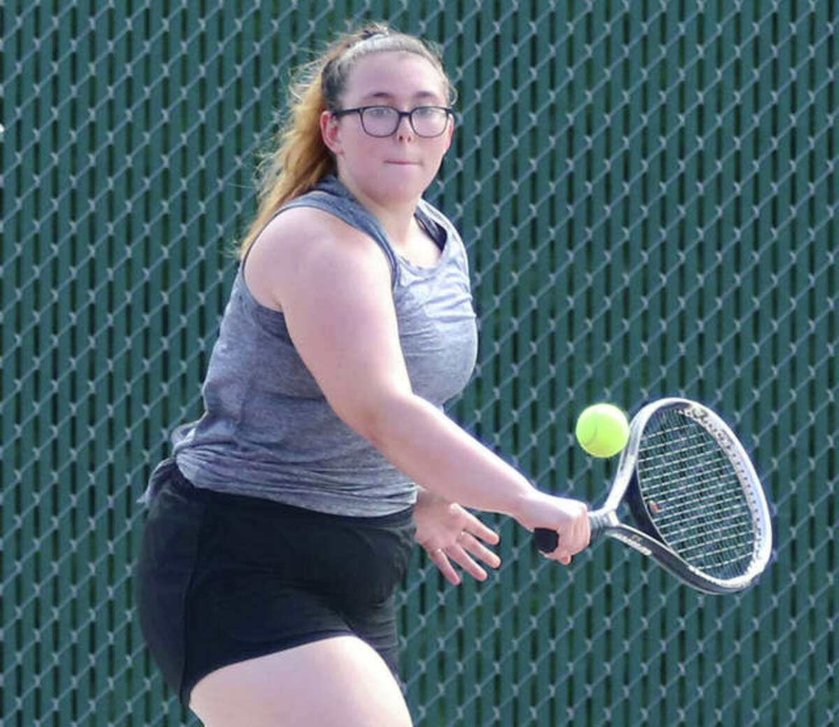 Alton senior Lydia Criveau hits a backhand during the Redbirds' first practice of the season Monday at the AHS courts in Godfrey.