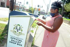 Aurelia William-Philpotts, of Stratford, drops her absentee ballot for Tuesday's primary elections into a state ballot drop box outside of Stratford Town Hall, in Stratford, Conn. Aug. 10, 2020. Among the primary races is one for Stratford Democratic Registrar of Voters.