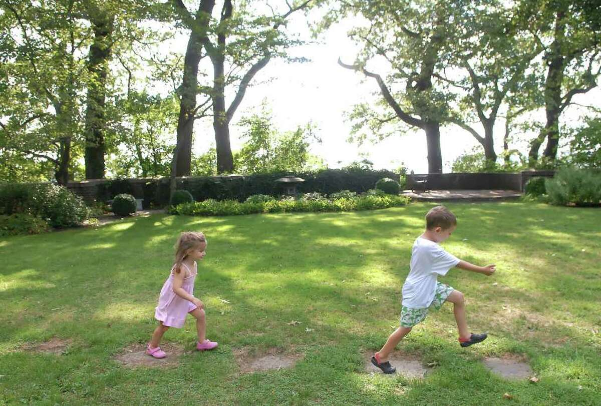 """Two young children play in the Secret Garden at Greenwich Point, Thursday afternoon, August 26, 2010. The official name of the garden is the Seaside Garden but because it is in an out of the way location on a small bluff on the northwestern side of the point, most visitors refer to it as the """"Secret Garden."""""""