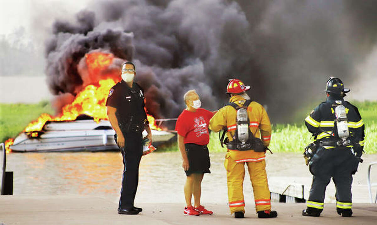 A man talks to firefighters around 5:30 p.m. Monday evening in the public boat launch area of the Alton Marina as a Bayliner boat burns out of control in the water. One man, who apparently had some connection to the boat, was injured and lying on the ground when firefighters arrived. An Alton Fire Department ambulance transported him to a local hospital. His condition was unknown. Alton firefighters appeared to be just letting the boat fire burn itself out since it was fully engulfed in flames when they arrived and was near nothing else that it could damage. Dozens of people lined the top of the levee watching and taking videos of the fire and heavy black smoke.