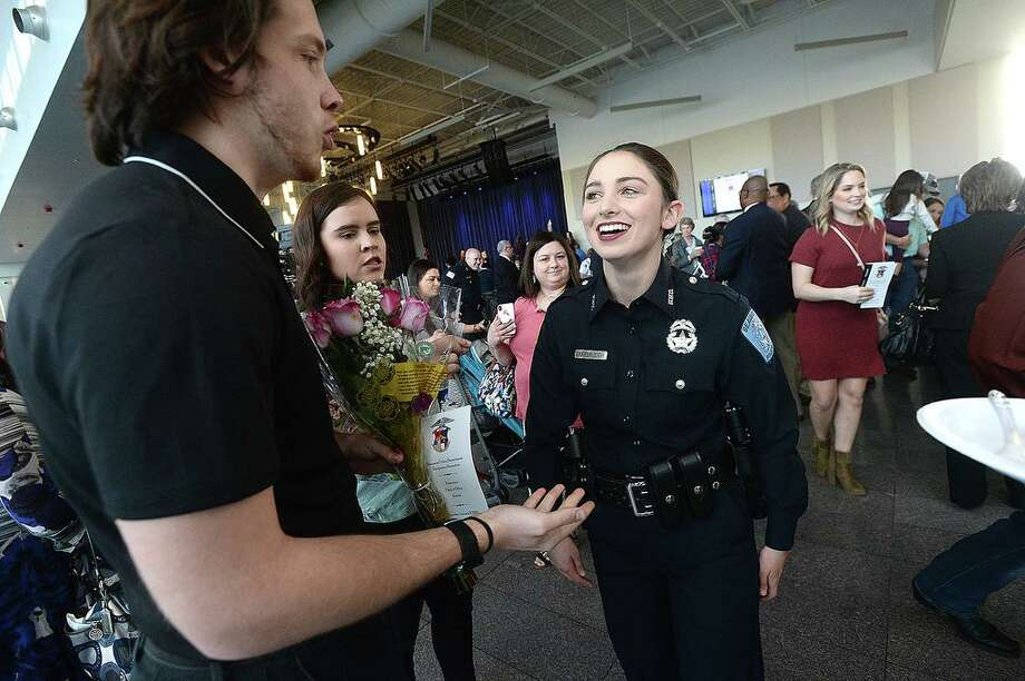 Beaumont Police officer Sheena Yarbrough talks with her boyfriend Tyler Powell, who brought flowers to congratulate her after joining 11 others sworn into office during a milestones ceremony Tuesday at the Event Centre. Twelve new officers were sworn in, officer Cody Foote was recognized for his promotion to Sergeant, and other officer and civilian awards were presented during the event. Photo taken Tuesday, January 8, 2019 Photo by Kim Brent/The Enterprise Photo: Kim Brent/The Enterprise