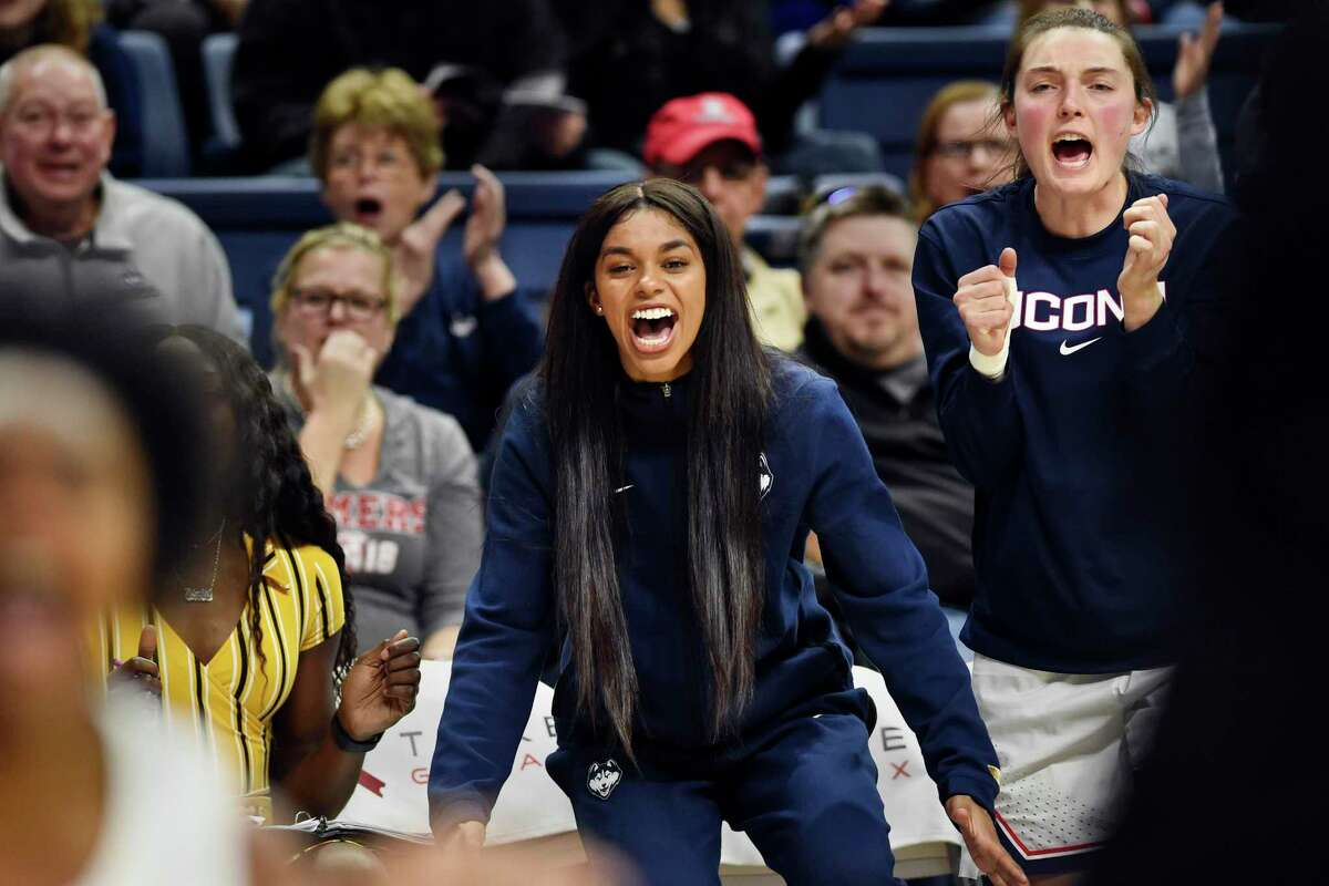 Connecticut's Evina Westbrook, center, cheers for her team from the bench during the second half of a women's NCAA college basketball game against California, Sunday, Nov. 10, 2019, in Storrs, Conn. Westbrook, a transfer student, was denied immediate eligibility by the NCAA to play this season. UConn is appealing the decision. (AP Photo/Stephen Dunn)