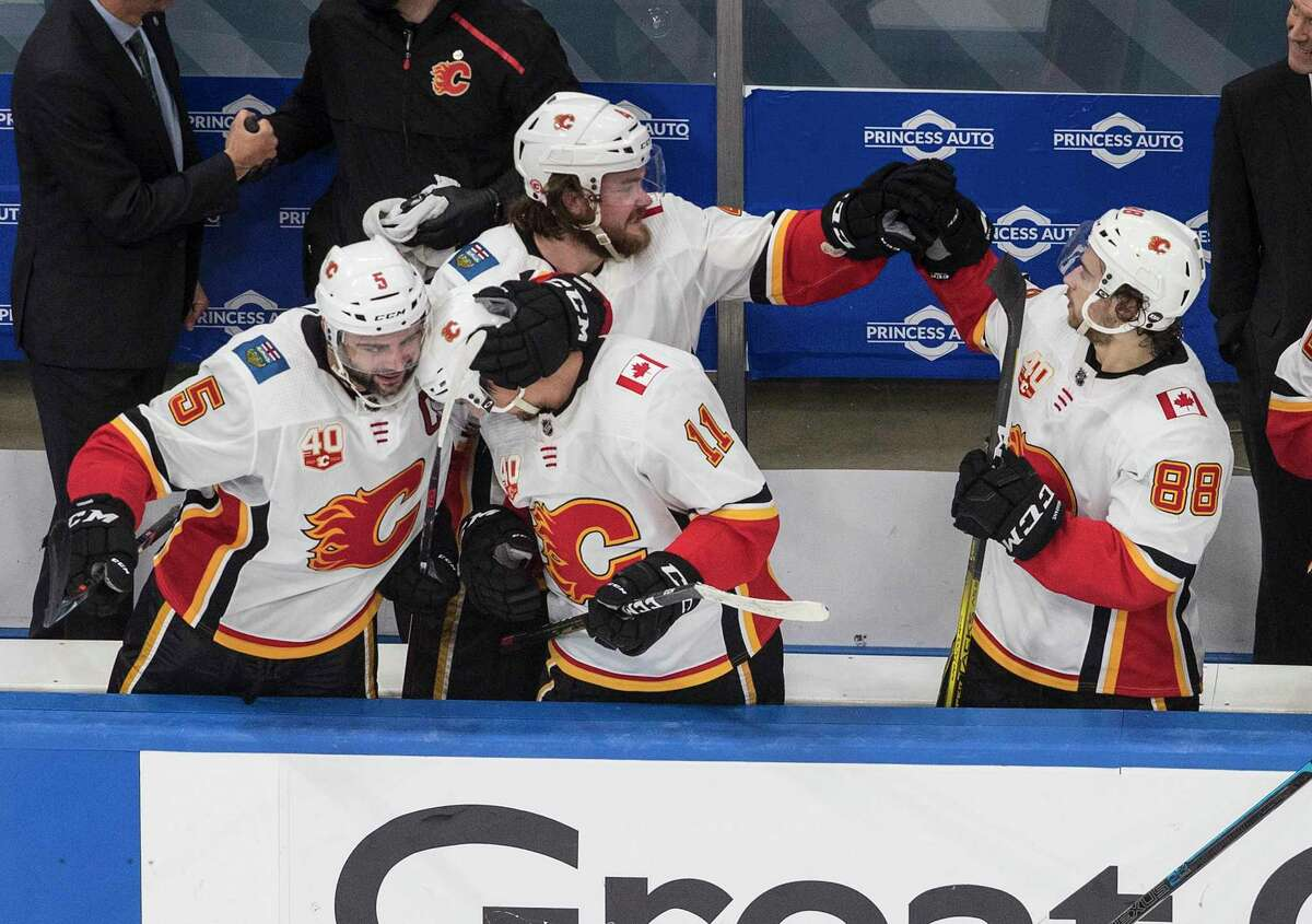 Calgary Flames players celebrate their 4-0 win over the Winnipeg Jets following an NHL qualifying round game, in Edmonton, Alberta, Thursday, Aug. 6, 2020. (Jason Franson/The Canadian Press via AP)