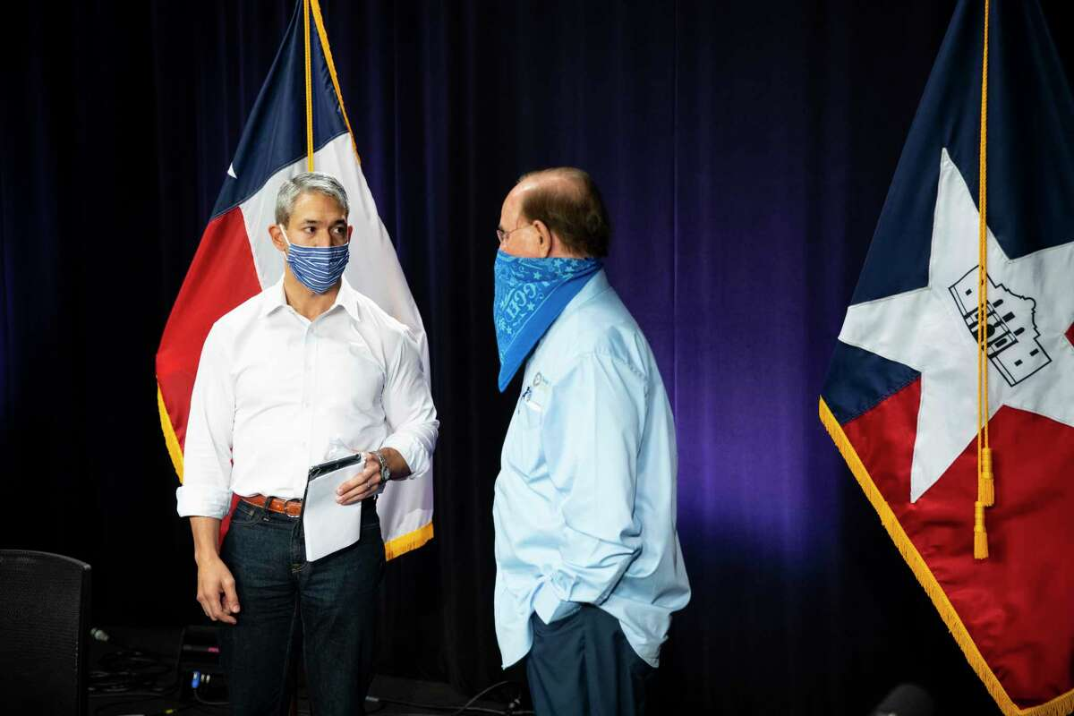 Mayor Ron Nirenberg, left, and Bexar County Judge Nelson Wolff speak to one another following a press briefing on the Coronavirus in San Antonio, Texas, U.S., on Monday, August, 10, 2020.