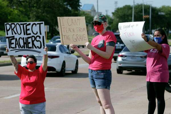 Cy-Fair teachers, staff and parents gather with protest signs at the main entrance to the district administration building against the COVID-19 teaching requirements before a Cy-Fair school board meeting Monday, Aug. 10, 2020 in Houston, TX.