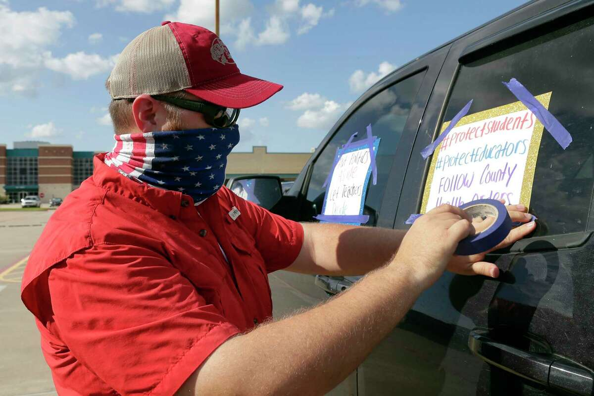 A Cy-Fair teacher tapes protest signs to his pick up truck in the parking lot of the district administration building before a Cy-Fair school board meeting Monday, Aug. 10, 2020 in Houston, TX.