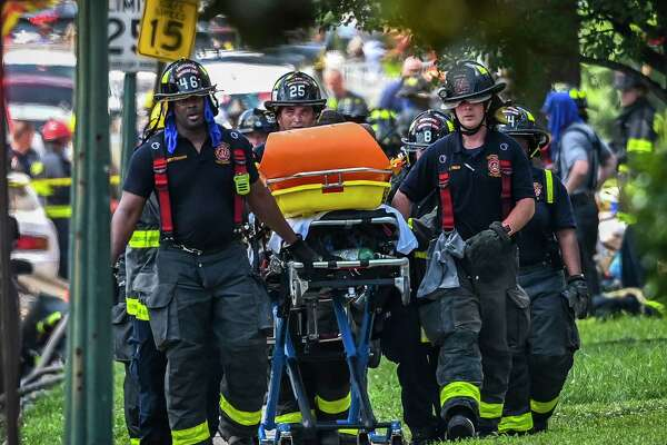 Paramedics wheel a person away from the scene of an explosion that destroyed three homes and killed a person in Baltimore on Monday, Aug. 10, 2020.