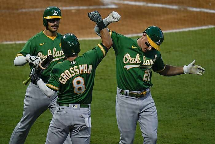 Oakland Athletics' Matt Chapman, right, celebrates his two-run home run with Robbie Grossman and Matt Olson during the third inning of a baseball game against the Los Angeles Angels, Monday, Aug. 10, 2020, in Anaheim, Calif. (AP Photo/Jae C. Hong)