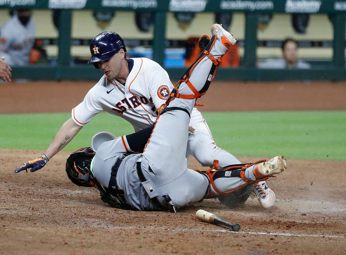 Houston Astros Josh Reddick collides with San Francisco Giantscatcher Chadwick Tromp at home after Michael Brantley reached on a fielder's choice out during the seventh inning of an MLB baseball game at Minute Maid Park, Monday, August 10, 2020, in Houston.