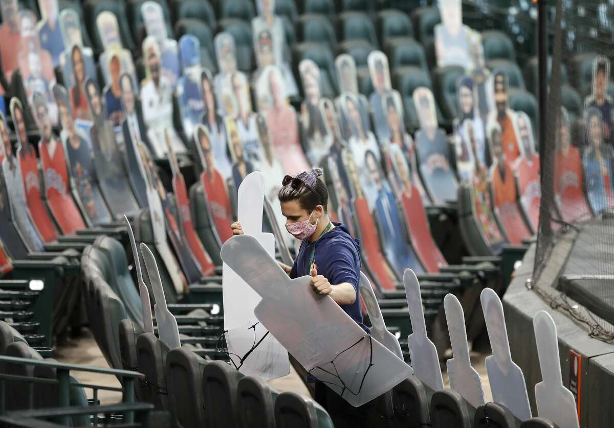 Houston Astros team photographer Alex Bierens de Haan places fan cutouts in the Diamond Club seats during batting practice before the start of an MLB baseball game at Minute Maid Park, Monday, August 10, 2020, in Houston.
