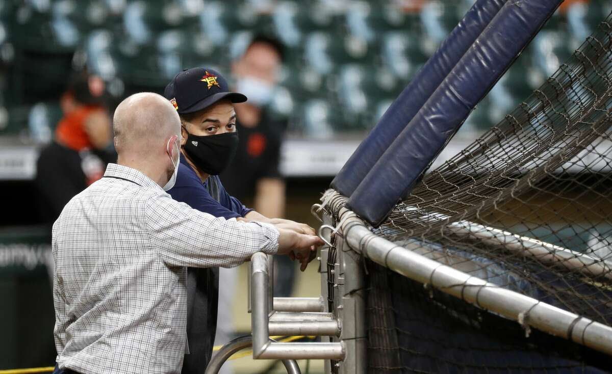 Houston Astros hitting coach Alex Cintron talks with general manager James Click during batting practice before the start of an MLB baseball game at Minute Maid Park, Monday, August 10, 2020, in Houston.
