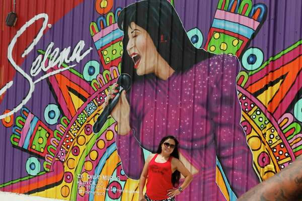 Mari Corral poses for a photograph taken by her friend Leroy Casanova Jr, in front of mural of Selena on the side of Alamo Candy Co. building on Saturday.