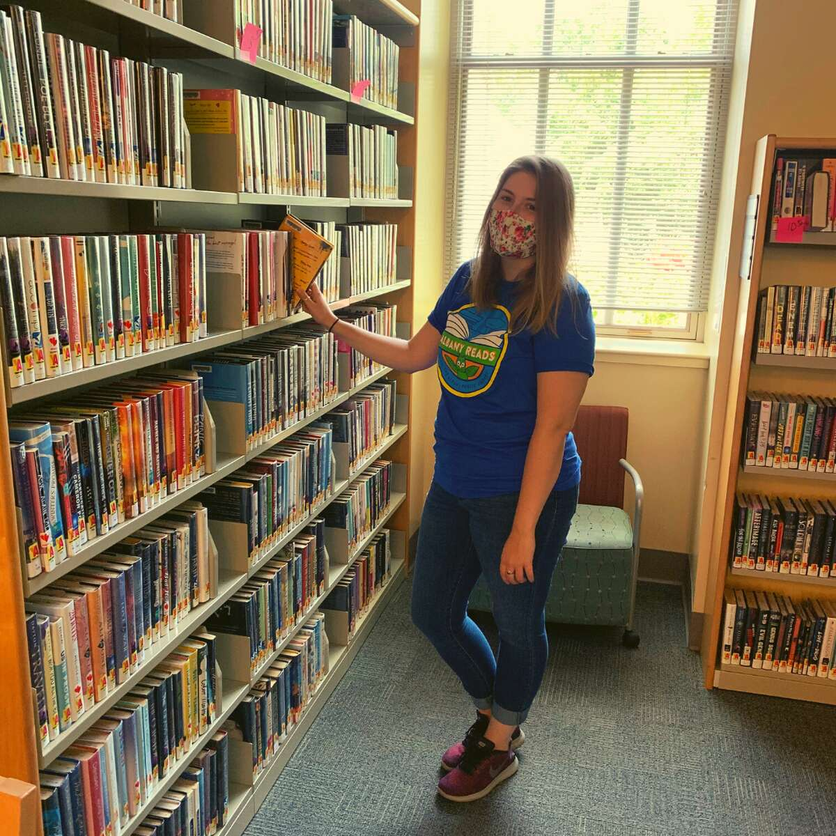 A staffer works on a shelving and weeding project at the Pine Hills Branch earlier this summer. Since the buildings are closed to the public right now, staff are spending some time getting the vast collections in tip-top shape. Credit: Albany Public Library