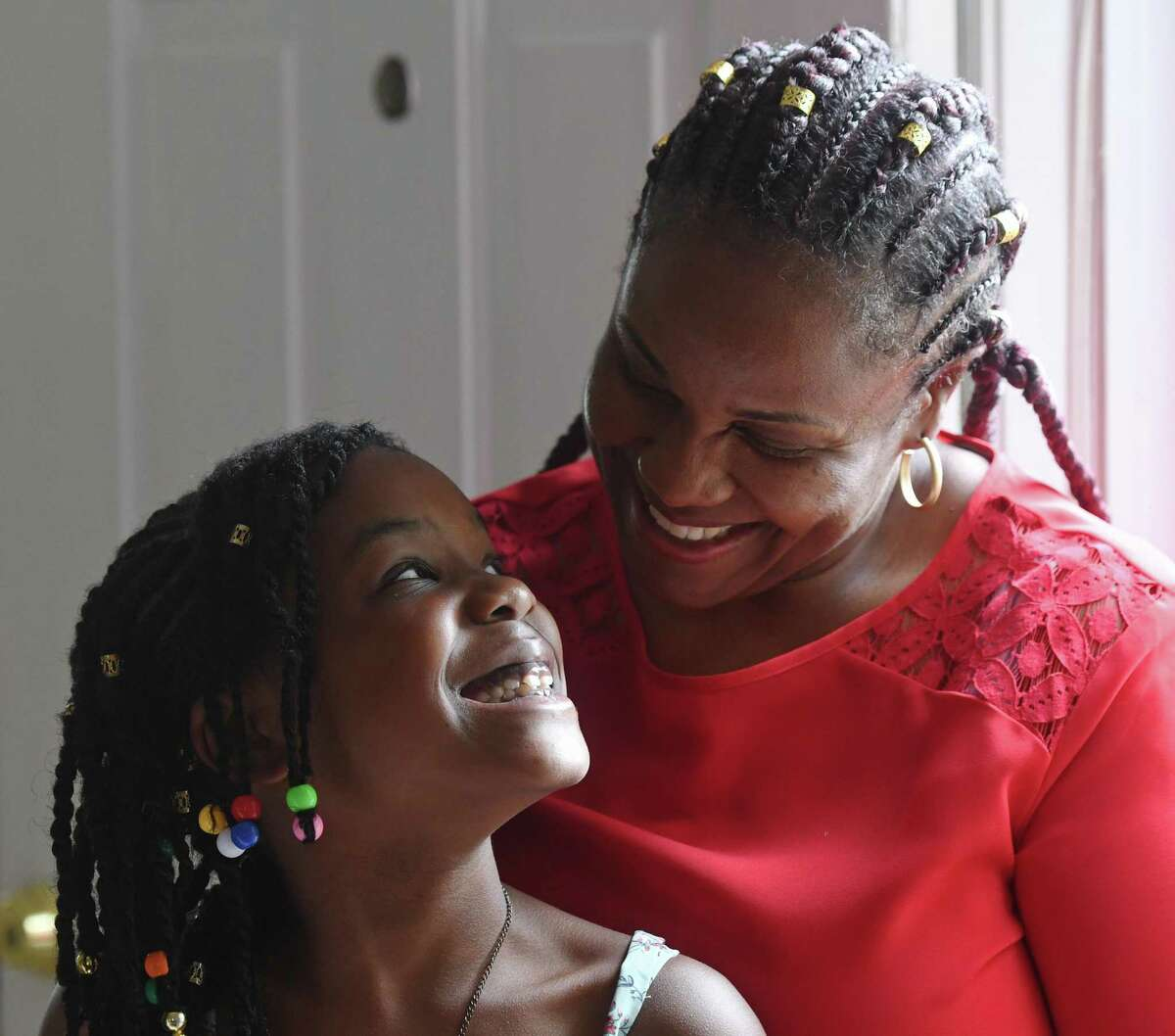 Ghislaine Germain with her daughter, Regina Renodo, 7, at their home in Stamford on Thursday. Renodo was rescued from drowning off West Beach by a police officer and emergency room nurse in early July.