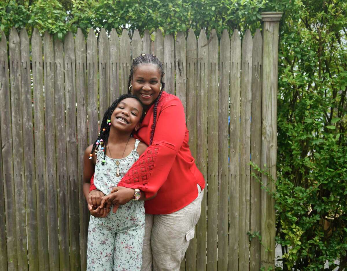 Ghislaine Germain poses with her daughter, Regina Renodo, 7, at their home in Stamford on Thursday. Renodo was rescued from drowning off West Beach by a police officer and emergency room nurse in early July.