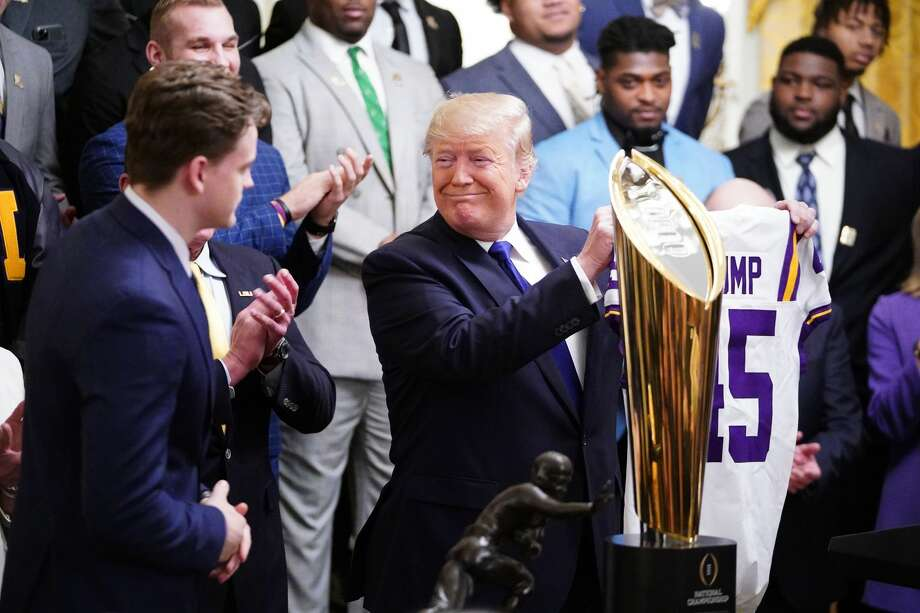 Tigers Quarterback Joe Burrow gives US President Donald Trump a team jersey as they take part in an event honoring the 2019 College Football National Champions, the Louisiana State University Tigers, in the East Room of the White House in Washington, DC, on January 17, 2020. (Photo by MANDEL NGAN / AFP) (Photo by MANDEL NGAN/AFP via Getty Images) Photo: MANDEL NGAN/AFP Via Getty Images