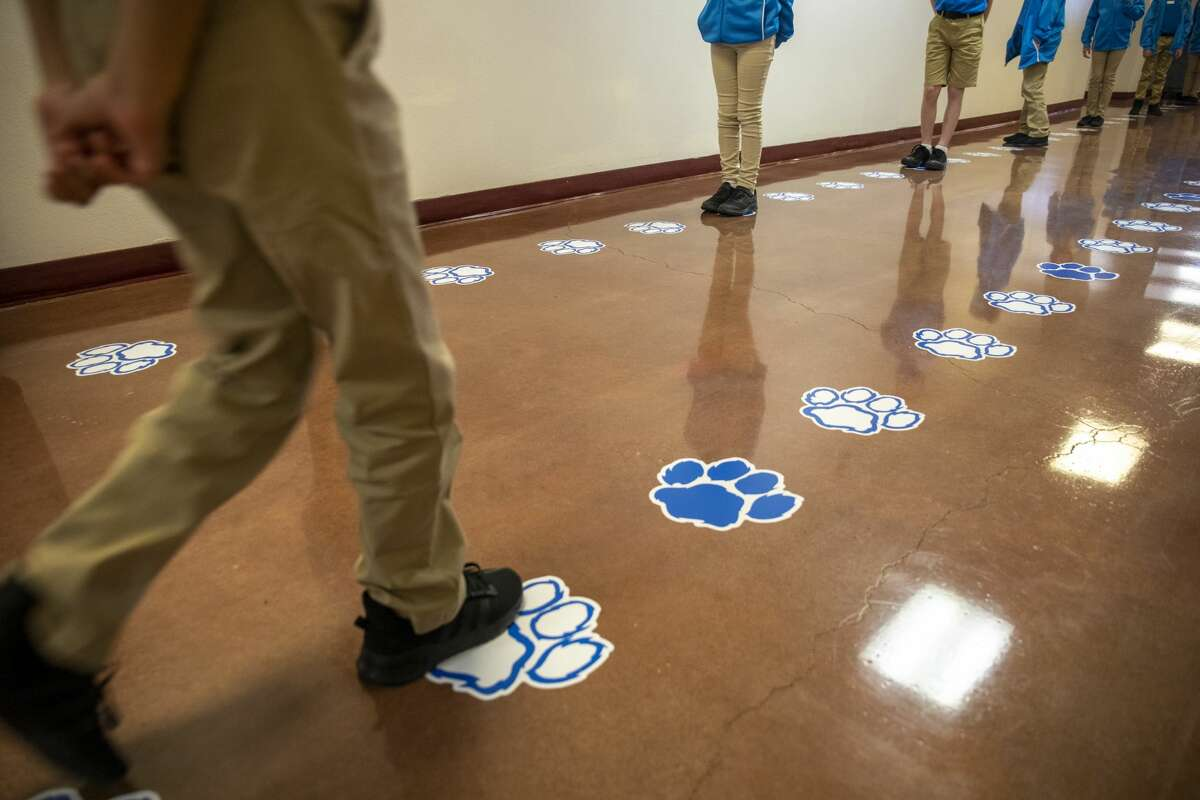 Students line up six feet apart on blue paws Tuesday, Aug. 11, 2020 at IDEA Travis Academy.