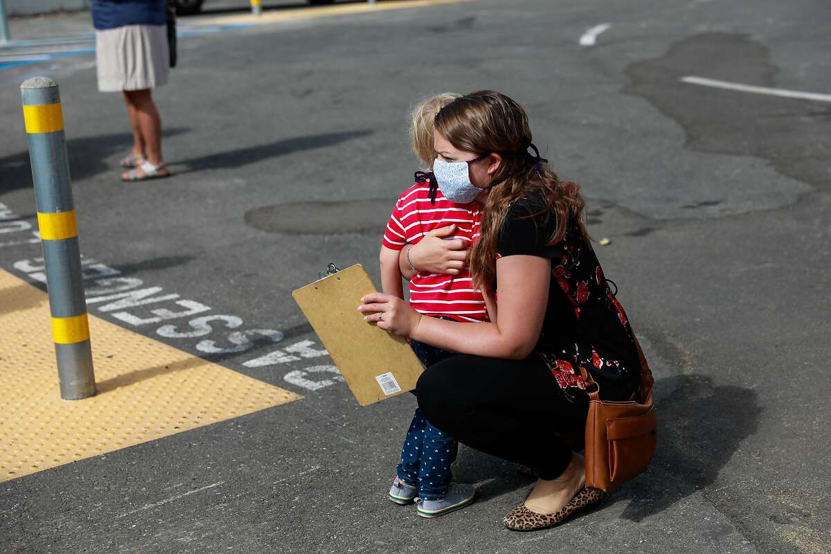 A woman embraces her child as they wait to pick up a computer to take home at Sankofa Academy on the first day of school on Monday, Aug. 10, 2020 in Oakland, California.