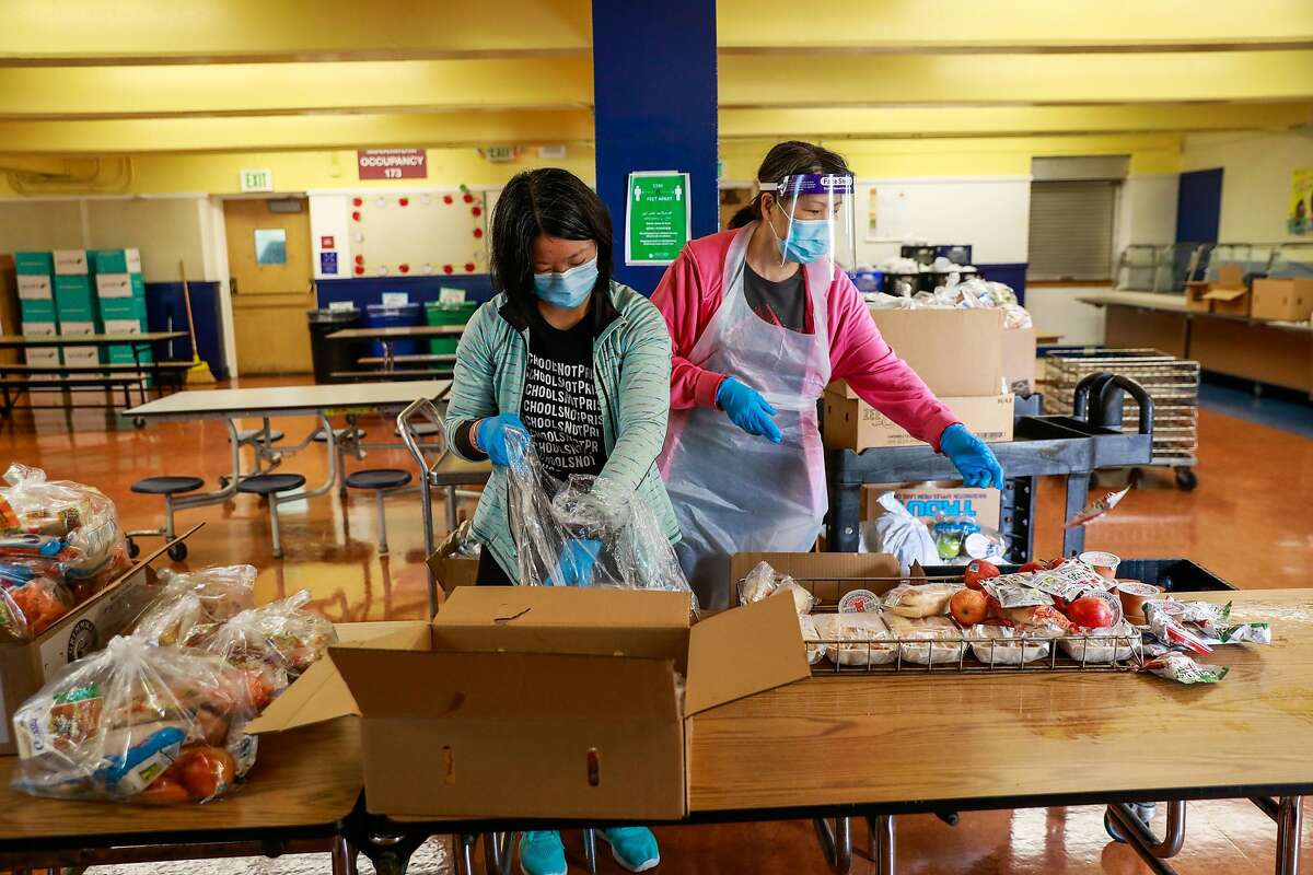 Rachel Huang and Wendy Li (right) prepare bagged lunch for students to take home at Sankofa Academy on the first day of school on Monday, Aug. 10, 2020 in Oakland, California.