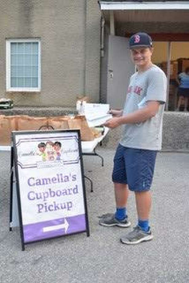 Evan Carlson of New Milford, 17, is a regular volunteer at the non-profit organization Camella's Cupboard. He recently conducted an athletic shoe fundraiser, collecting gently used shoes that he earned money for and then donated to Camella's Cupboard. Photo: Courtesy Of The Carlsons / / Danbury News Times Contributed