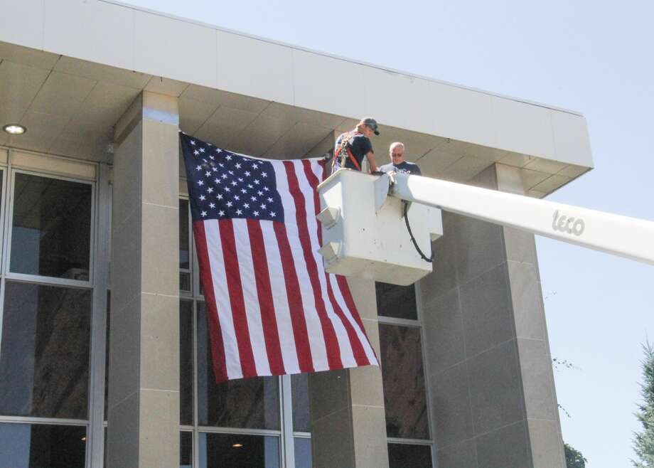Todd Talaski, owner of Talaski Building Movers and a member of the Huron County Board of Commissioners, purchased an 8-by-12-foot American flag and hung it on the front of the Huron County Courthouse on Tuesday afternoon. Talaski worked with his son, Bryce, install the flag, which will remain on the courthouse until Veteran's Day. Photo: Mark Birdsall/Huron Daily Tribune