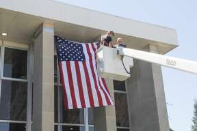 Todd Talaski, owner of Talaski Building Movers and a member of the Huron County Board of Commissioners, purchased an 8-by-12-foot American flag and hung it on the front of the Huron County Courthouse on Tuesday afternoon. Talaski worked with his son, Bryce, install the flag, which will remain on the courthouse until Veteran's Day.