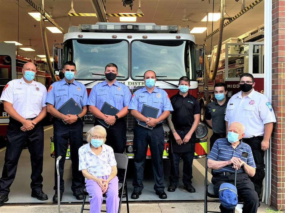 Four South Fire District first responders, along with two Hunter's Ambulance staff members and a Middlesex Health paramedic, saved the life of an 80-year-old city woman (seated) who went into cardiac arrest July 10 at her home. After undergoing heart surgery, she is doing well. Photo: South Fire District Photo
