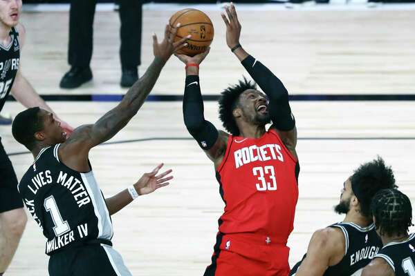 San Antonio Spurs guard Lonnie Walker IV (1) blocks a shot by Houston Rockets forward Robert Covington (33) during the first half of an NBA basketball game Tuesday, Aug. 11, 2020, in Lake Buena Vista, Fla. (Kim Klement/Pool Photo via AP)