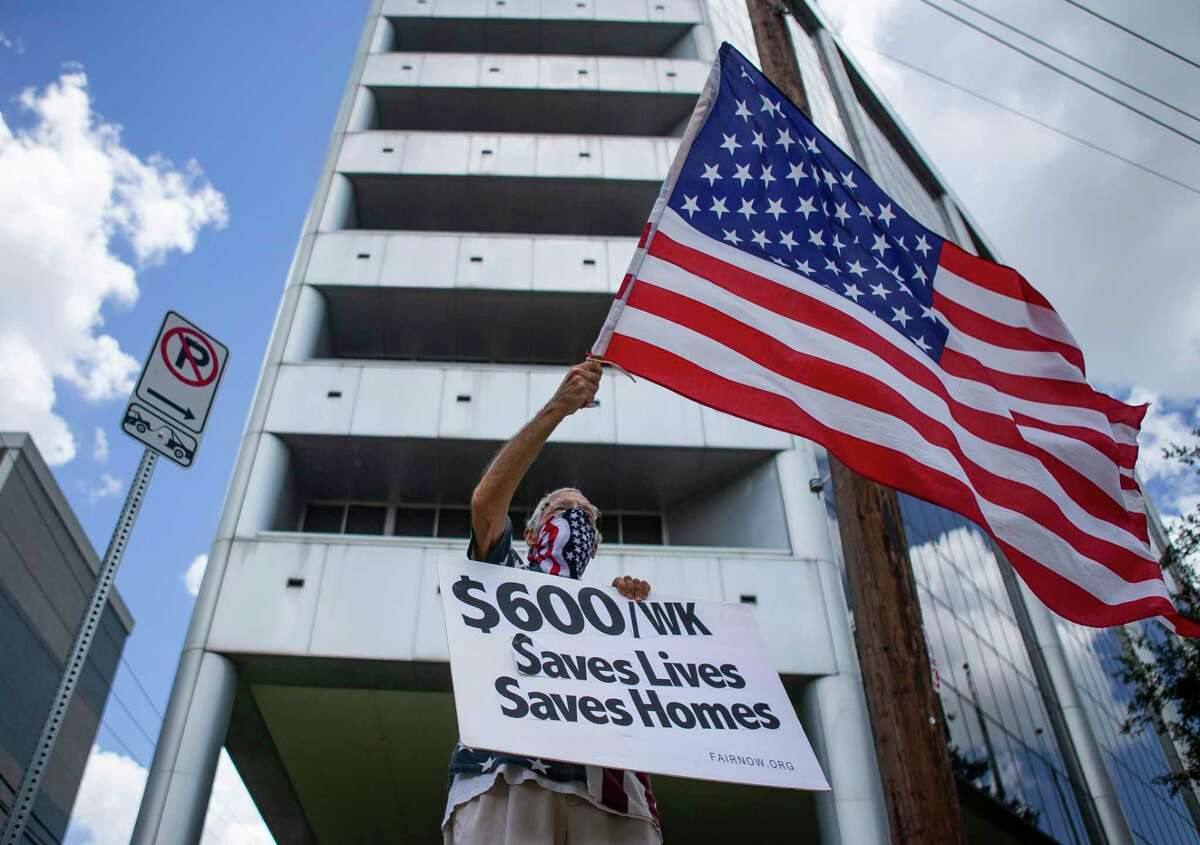 Ira B Dember waves a flag and holds a sign in solidarity with unemployed workers with the organization UNITE Here, a union that represents hospitality workers, along Memorial Drive on Tuesday, Aug. 11, 2020, outside of Senator John Cornyn's office in Houston. The demonstration involved a food distribution for unemployed hospitality workers who have watched their $600 unemployment benefits expire.