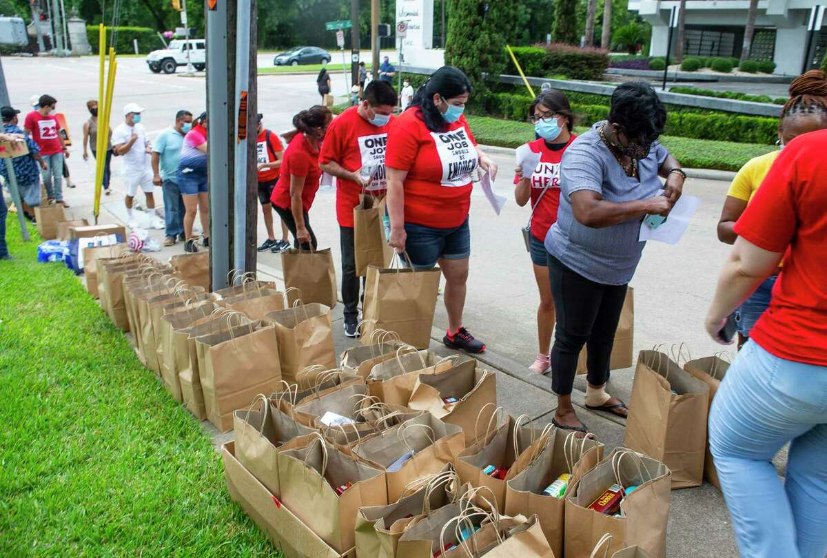 Food is distributed to unemployed people by the organization UNITE Here, a union that represents hospitality workers, along Memorial Drive on Tuesday, Aug. 11, 2020, outside of Senator John Cornyn's office in Houston. The demonstration involved a food distribution for unemployed hospitality workers who have watched their $600 unemployment benefits expire.