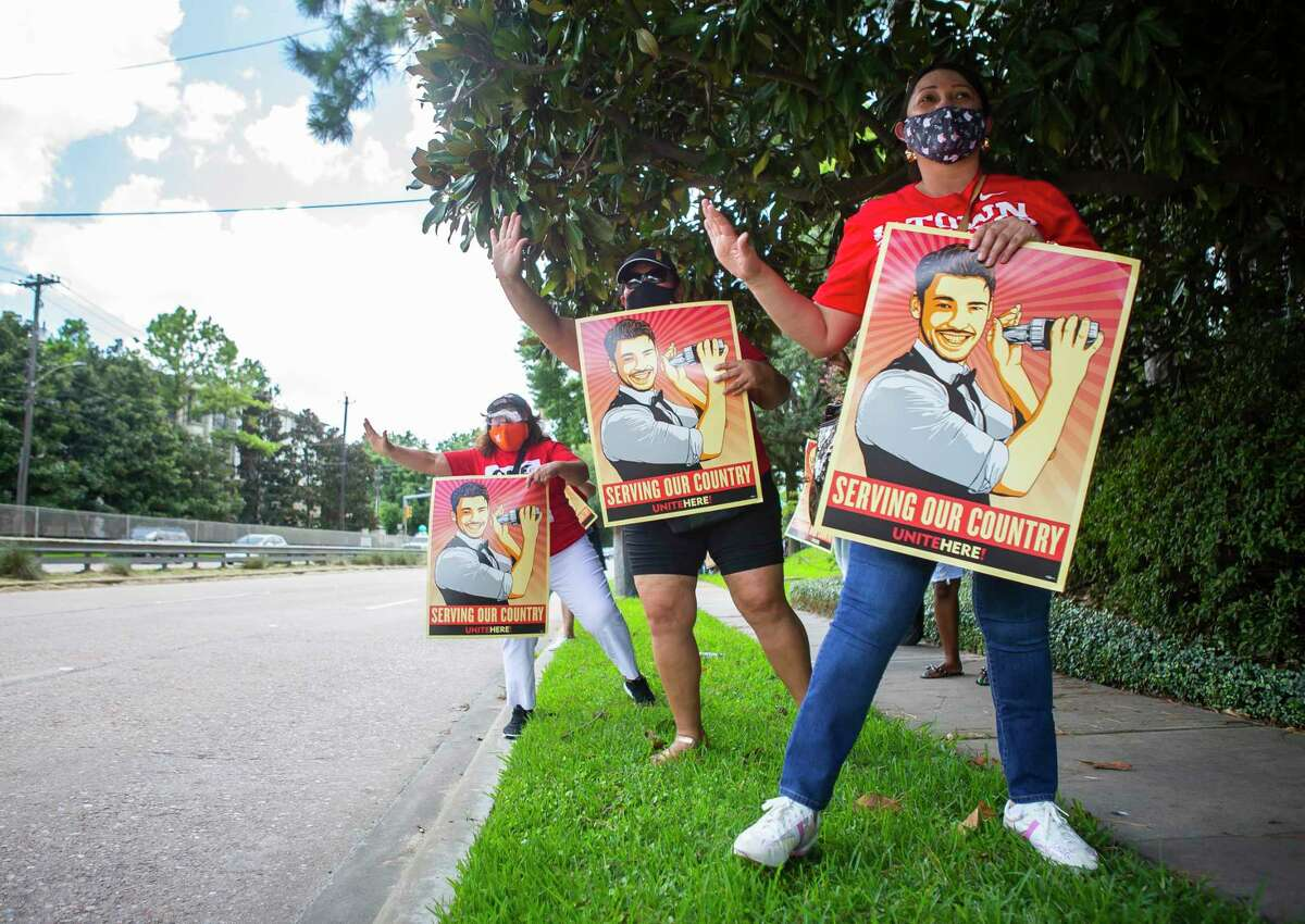 Melva Lopez, left, Maria Sandoval and Ana Betancourt, who work as housekeepers and are currently unemployed, urge drivers to honk their horns as they demonstrate with UNITE Here, a union that represents hospitality workers, along Memorial Drive on Tuesday, Aug. 11, 2020, outside of Senator John Cornyn's office in Houston. The demonstration involved a food distribution for unemployed hospitality workers who have watched their $600 unemployment benefits expire.