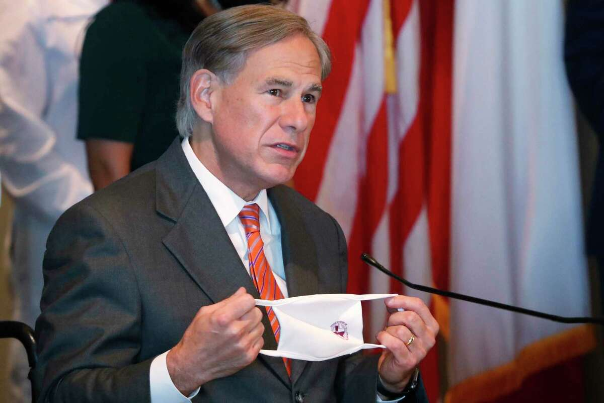 Texas Gov. Greg Abbott holds up mask as he talks about the importance of wearing face coverings to prevent the spread of COVID-19 during a news conference in Dallas, Thursday, Aug. 6, 2020. (AP Photo/LM Otero)