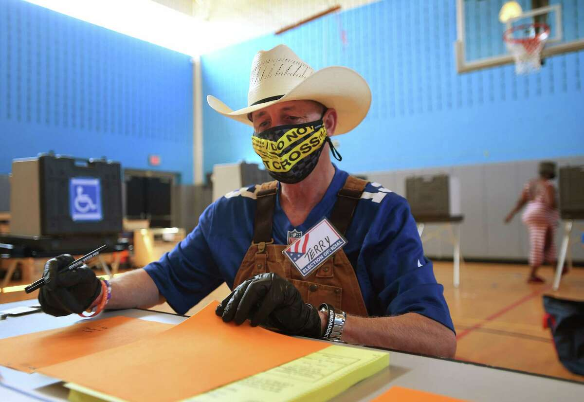 Republican poll worker Terry Sullivan, of Bridgeport, checks in voters during primary voting at Geraldine Johnson School in Bridgeport, Conn. on Tuesday, August 11, 2020. Masks not required for in-person voting Masks are not required for in-person voters, but they are for poll workers.