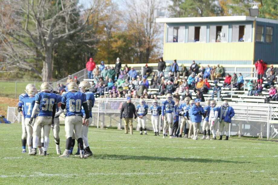 The Onekama football team huddles up in front of coaches and fans during a game last fall. (News Advocate file photo)