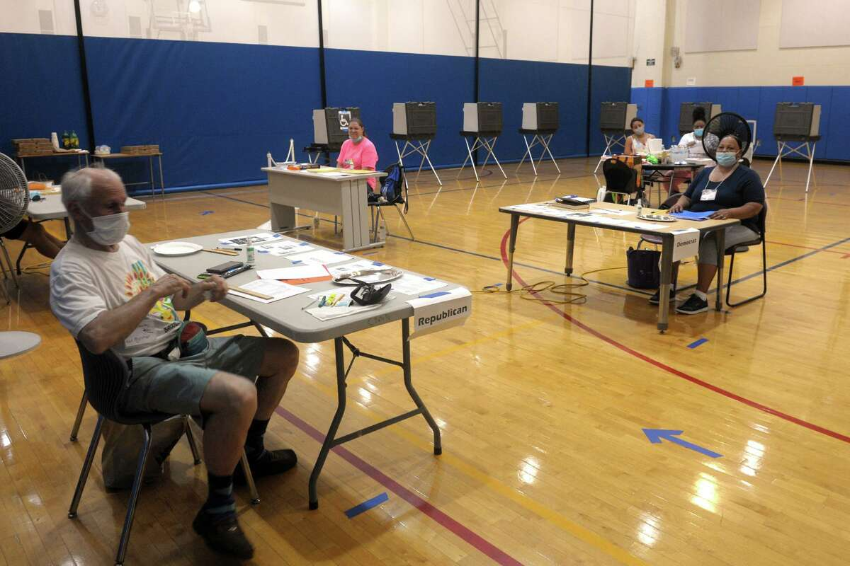 Registrars and poll workers wait for voters in the Batalla School gymnasium in Bridgeport before the August primary. What do I need to bring with me to vote? For most voters, any kind of preprinted form or ID with a photo is appropriate. If a voter does not have a photo ID, a paycheck stub or a utility bill is appropriate to show at the polls. If a voter doesn't have any of that, they may sign an affidavit, under the potential criminal penalties of issuing a false statement. For first-time voters who registered by mail, current and valid photo IDs, utility bills or a paycheck stub with their name and address are required of the very small number this would affect. Can I register to vote on Election Day? Connecticut allows Election Day registration for those who are not registered or are moving. Election Day registration is not available at polling places. More information can be found at: portal.ct.gov/SOTS/Election-Services/Election-Day-Registration/Election-Day-Registration.