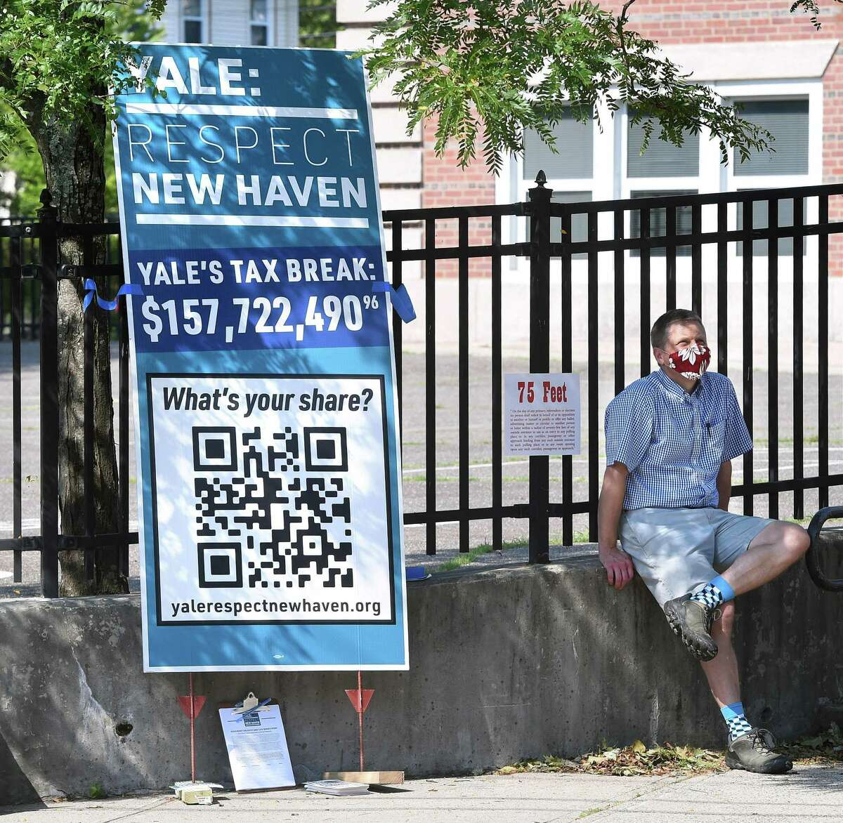 New Haven Alder Adam Marchand sits outside of the Edgewood School polling place in New Haven on Aug. 11, 2020, next to a sign about Yale University's tax exemption.
