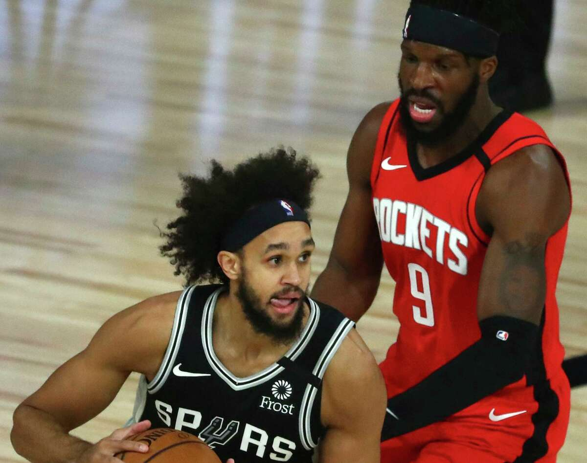 San Antonio Spurs guard Derrick White, left, handles the ball while Houston Rockets forward DeMarre Carroll, right, defends during the first half of an NBA basketball game Tuesday, Aug. 11, 2020, in Lake Buena Vista, Fla. (Kim Klement/Pool Photo via AP)