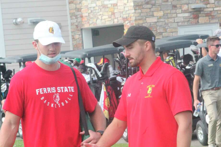 Peter Firlik (right), a member of the 2018 men's basketball national championship team, gets ready for a round of golf at the recent basketball golf outing at Katke Golf Course. (Pioneer photo/John Raffel)