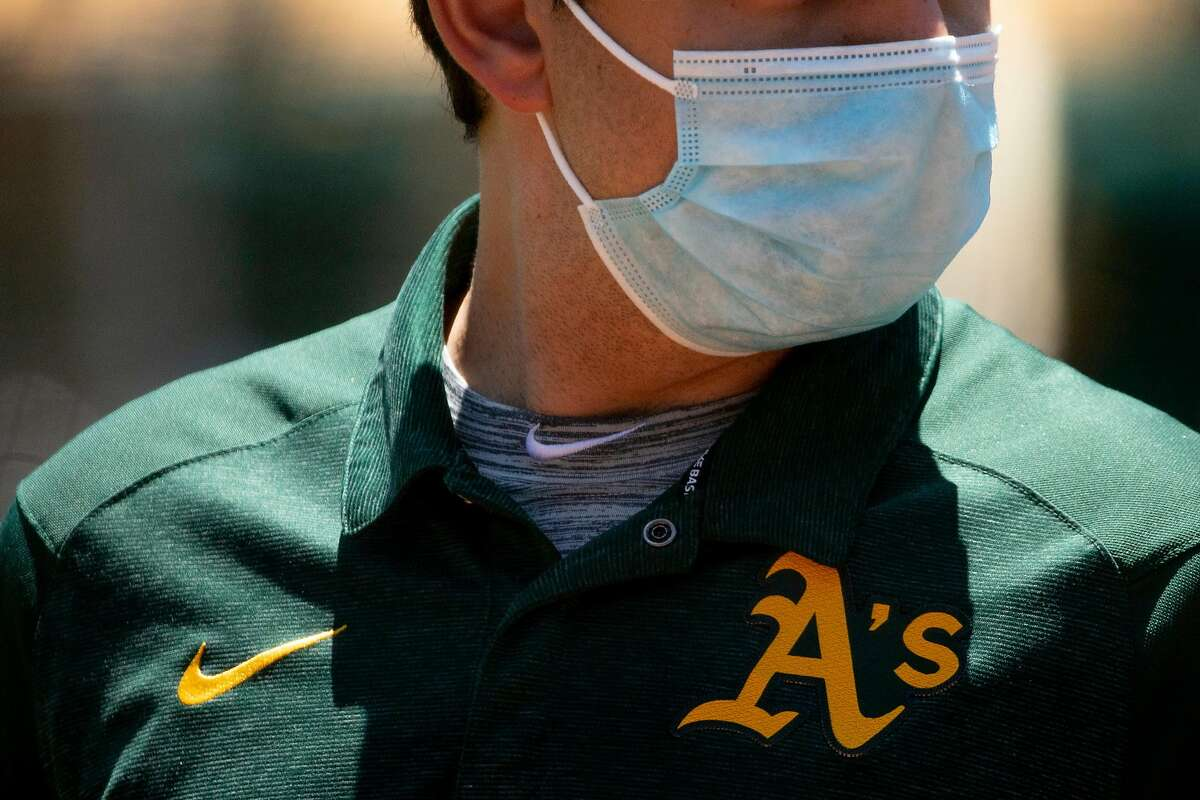 An Oakland A's employee sports a face mask during an Oakland A's training camp workout at O.Co Coliseum in Oakland, Calif. Tuesday, July 7, 2020. Due to COVID-19, the 2020 MLB season has been postponed with players just beginning to return for warmups and practices while wearing masks and keeping social distance.